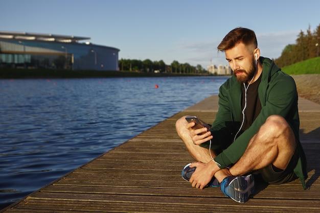 人、現代のテクノロジー、コミュニケーションのコンセプト。湖の前に足を組んで座って携帯電話を使用して音楽を聴いているスニーカーでハンサムな若い無精ひげを生やした男性のヒップスターの屋外ビュー