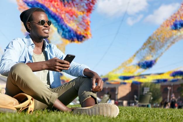 人、現代技術、リラクゼーション、ライフスタイルのコンセプト。スタイリッシュな服と色合いのファッショナブルな黒人男性。携帯電話を使って緑の芝生でリラックスし、人々とのコミュニケーションに喜びを感じています。