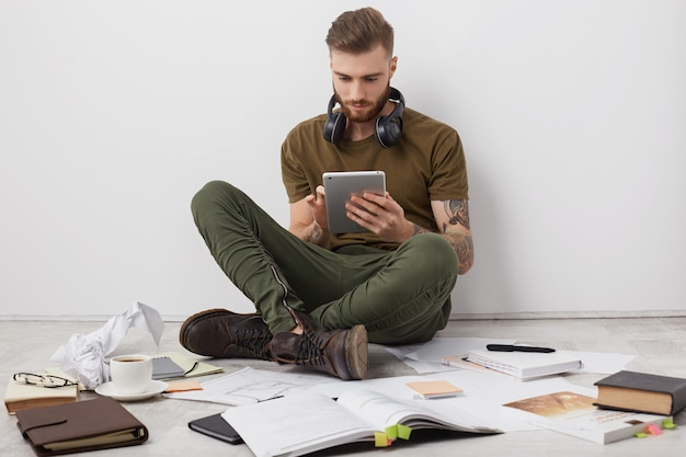 People, modern technology and education concept. bearded stylish man wears boots, sits crossed legs on floor,