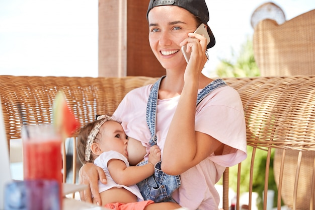 People, motherhood and family concept. little baby feeds her mother`s breast milk, recieves love and care. Free Photo