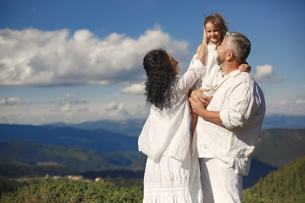 People in a mountain. grandparents with grandchildren. woman in a white dress.