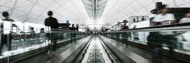 People on a moving walkway in a passenger terminal at the airport