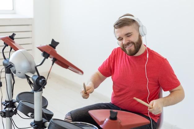 사람, 음악, 취미 개념 - 여가 시간에 전자 드럼 세트를 연주하는 남자.