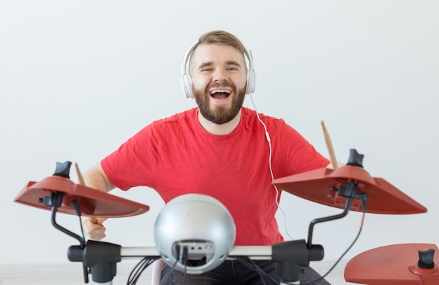 사람, 음악, 취미 개념 - 흰색 헤드폰을 끼고 밝은 배경 위에 드럼을 치는 남자.