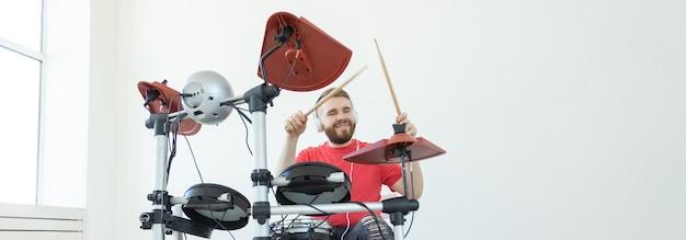 사람, 음악, 취미 개념 - 전자 드럼 키트를 연주하는 터프한 남자. 복사 공간, 배너