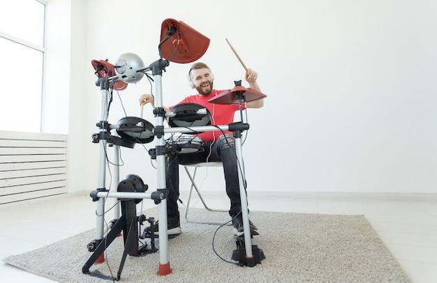 사람, 음악, 취미 개념 - 전자 드럼 키트를 연주하는 터프한 남자.