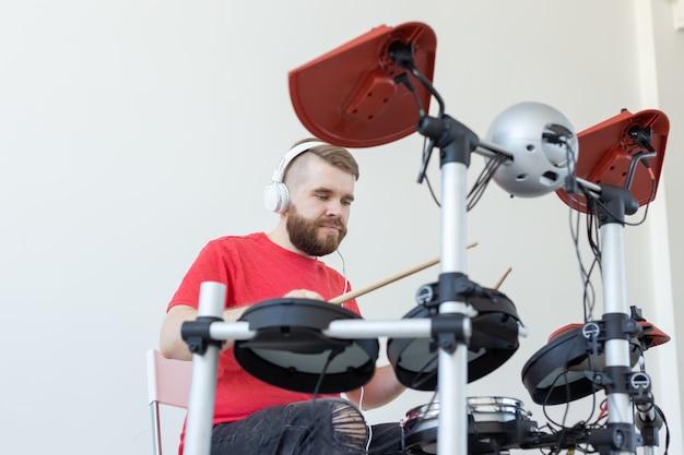 人、音楽、趣味のコンセプト-ドラムを演奏する若い男。