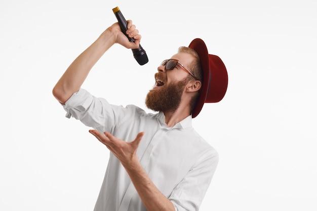 사람, 음악, 재미, 쇼 및 엔터테인먼트 개념. 빨간색 둥근 모자와 트렌디 한 음영을 입고 마이크에 두꺼운 수염이 노래하는 정서적 잘 생긴 세련된 빨간 머리 팝 아티스트