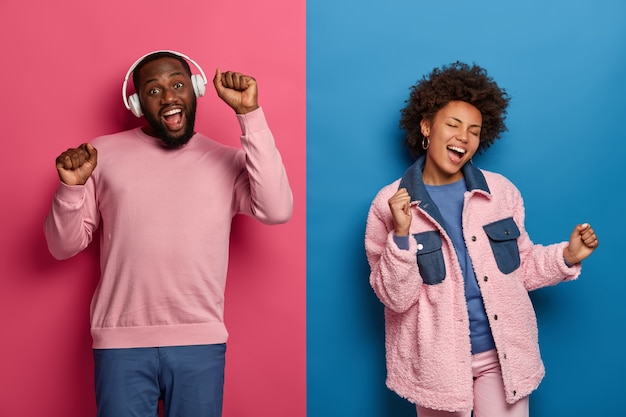 People, music and leisure concept. happy african american couple dances carefree, move actively and keep hands up, listen music in headphones, isolated on pink and blue wall, feel amused