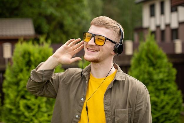人、音楽、テクノロジー、レジャー、ライフスタイル-屋外の緑の背景で彼の耳に手をかざして音楽を聴いているイヤホンを持つ流行に敏感な男