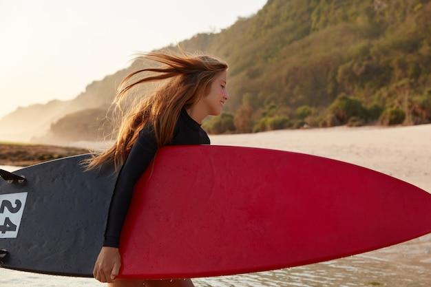 人、自然、アクティブなライフスタイルのコンセプト。幸せな濡れた若い女性の横向きのショットはサーフボードを運ぶ