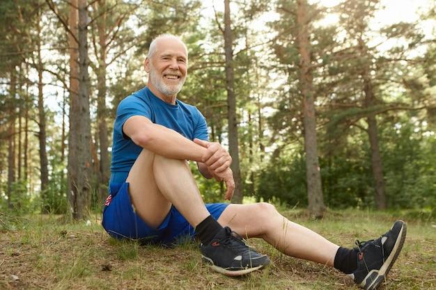 人、自然、スポーツ、レジャーのコンセプト。灰色の無精ひげを持った幸せなのんきな引退した男は、松林の草の上に快適に座って、ひじを膝の上に保ち、有酸素運動の後に屋外で休んでいます