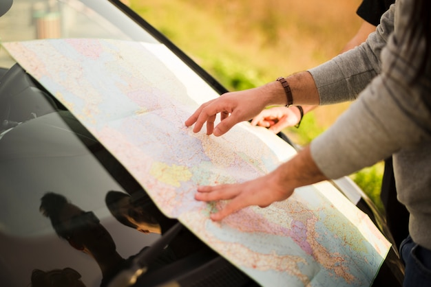 People navigating with map on a road trip