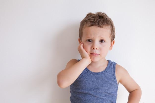 사람, 부정적인 감정, 건강 및 질병 개념. 슬픈 불행한 남자 아이는 고통스러운 화난 표정을 지으며 견딜 수없는 치통으로 고통받으며 뺨을 만지고 울 것입니다.