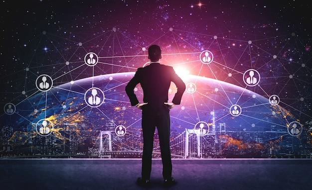 ピープルネットワークとグローバルコミュニケーションのコンセプト。国際的なビジネスを接続するためにソーシャルメディアプラットフォームによって世界中の多くの人々をリンクするコミュニティのモダンなグラフィックインターフェイスを持つビジネスマン。