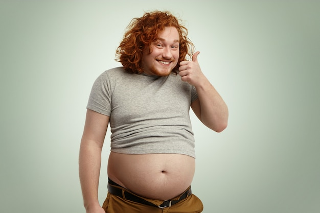 People, nutrition, body shape and healthy lifestyle concept. happy young plump chubby man with curly ginger hair and beard showing thumps up, saying he is doing okay while his belly sticking out