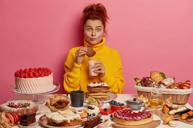 People, nutrition, calories, bakery concept. ginger girl in yellow jumper eats tasty oatmeal cookies and drink yoghurt, sits at table with many delicious cakes, doesn't keep to diet.