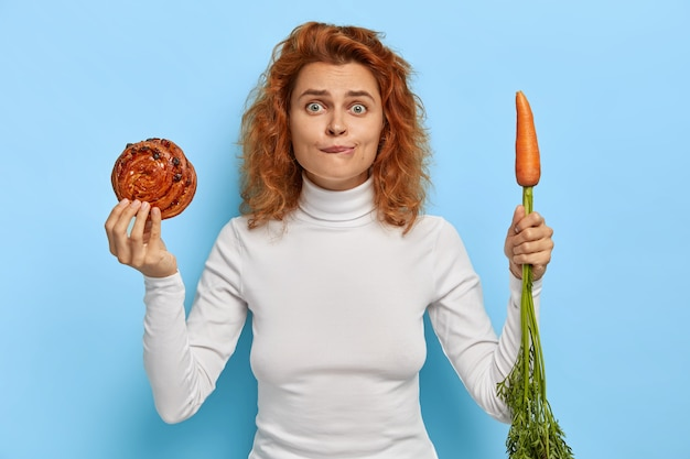 People, nutrition, dieting and junk food concept. embarrassed redhead woman holds fresh tasty bun and carrot, chooses between vegetable and confectionery, wears white turtleneck, stands indoor