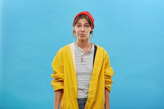 人、職業、顔の表情のコンセプト。疑いをもって彼女の唇を曲げ魅力的な若い女性はカジュアルな服装で家について仕事をします。黄色のルーズジャケットと赤い帽子でかわいい女性