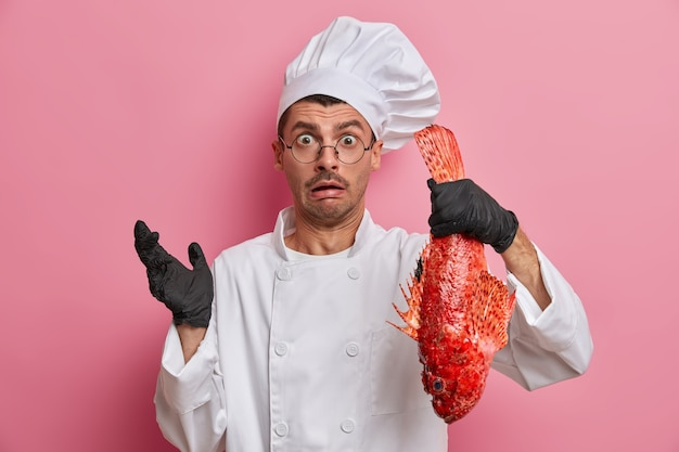 People, occupation, restaurant staff, catering concept. confused surprised cook holds big red sea fish in hand, prepares fresh meal for restaurant visitors