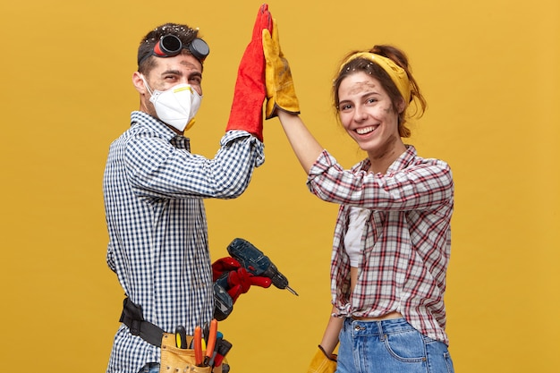 People, occupation, teamwork, cooperation concept. caucasian couple standing sideways doing construction works at home touching their hands together rejoicing their success and great results