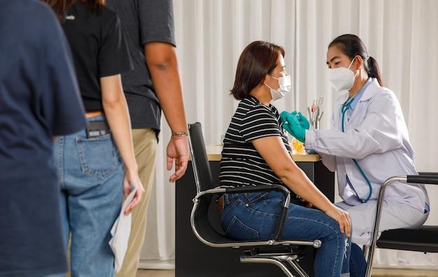 의사가 얼굴 마스크를 쓴 노인 여성에게 독감이나 폐렴 주사를 놓는 동안 다양한 연령대의 사람들이 연속으로 서서 백신 주사를 기다리고 있습니다. 코비드-19 또는 코로나바이러스 예방 접종 개념.