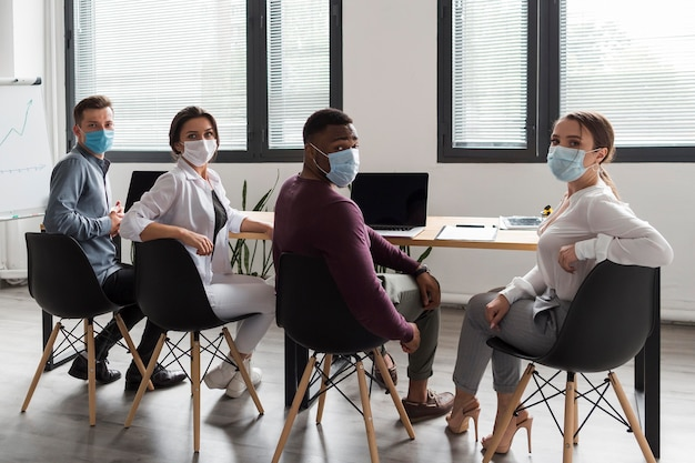 People in the office during pandemic working while wearing medical masks