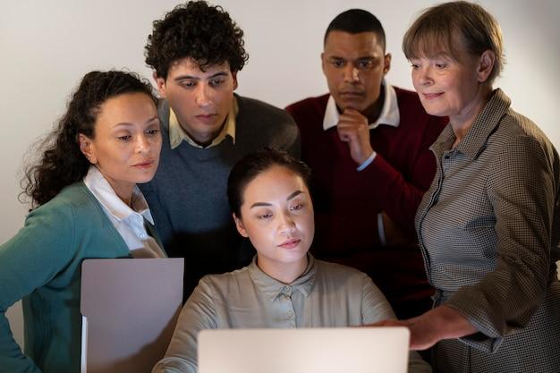 Persone in ufficio che lavorano fino a tardi