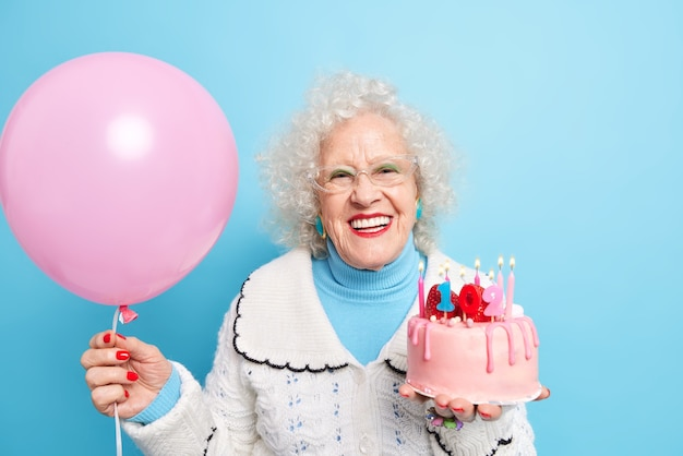 People old age partying and holidays concept. positive beautiful grandmother dressed in neat clothes celebrates her 102nd birthday holds inflated balloon and tasty cake
