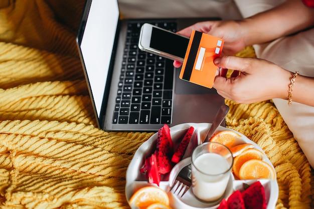 온라인 쇼핑 결제를 위해 신용 카드와 스마트 폰을 들고 손으로 침대에있는 사람들