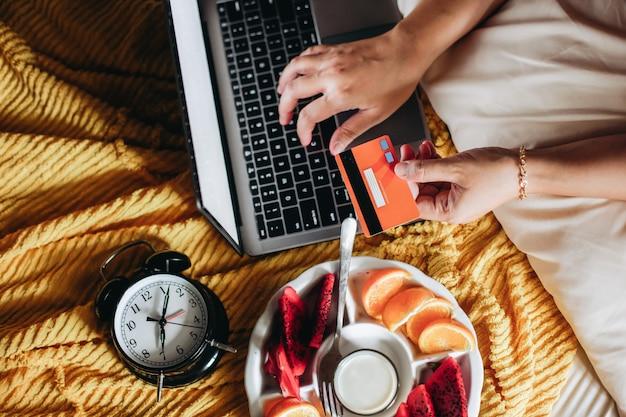 신용 카드를 들고 노트북 키보드에 입력하는 손으로 침대에있는 사람들
