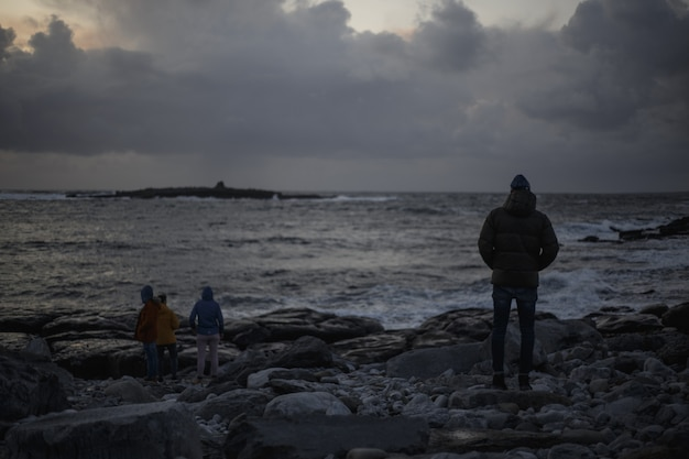 岩と雲と暗い海の景色の人々