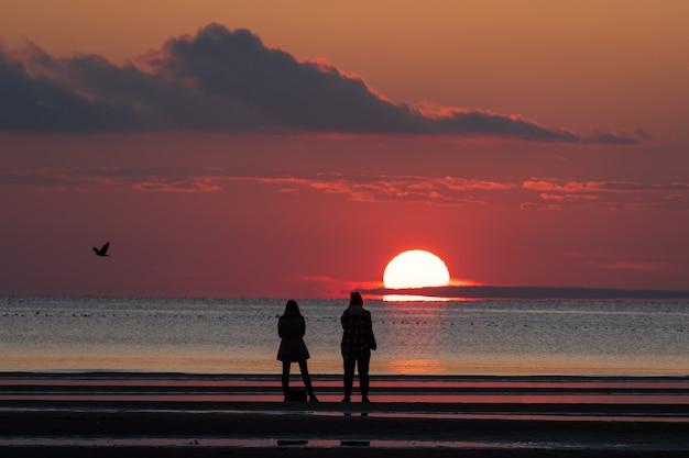 해변에 있는 사람들은 가을철에 아름다운 일몰을 즐깁니다. 바다와 화려한 하늘의 석양을 바라보세요