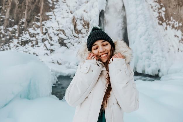 美しい自然を背景にした人々。山の晴れた天気。冬服の女の子が笑顔でフレームを覗き込みます。