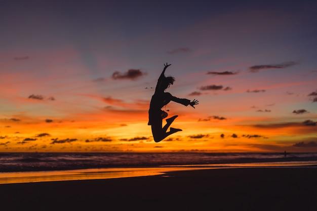 해질녘 해변에서 사람들입니다. 소녀는 석양을 배경으로 점프하고 있습니다.