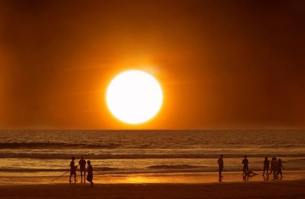 夕日、海、休暇で水の中のビーチの人々。