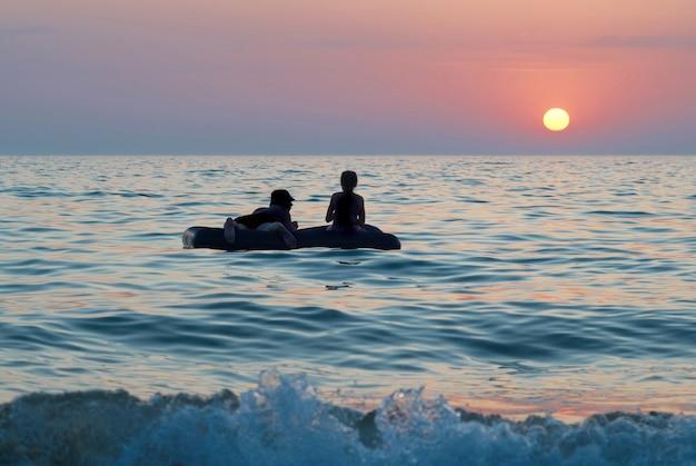 海に沈む夕日のいかだに乗っている人