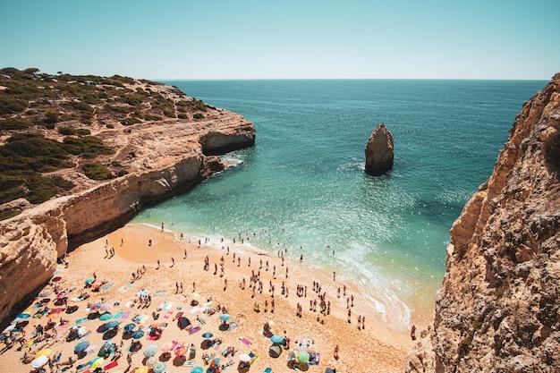 절벽과 잔잔한 바다 근처의 모래 해변에있는 사람들