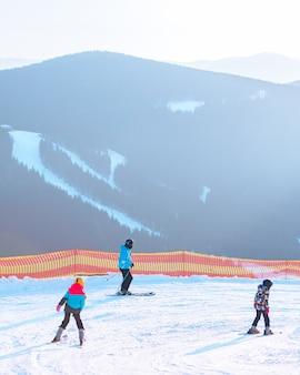 スキーリゾートの斜面の人々夕方の日没時間