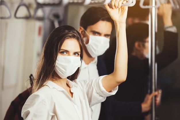 電車の中で人々はアンチウイルスマスクを着用し、ラッシュアワーに旅行します。すべての人の顔にマスクを付けたスカイトレイン内の乗客。