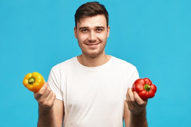 人、有機食品、栄養、菜食主義、健康的なライフスタイルのコンセプト。赤と黄色のピーマンを保持し、サラダを作るつもりの白いtシャツを着ているハンサムなポジティブな若い男性の肖像画