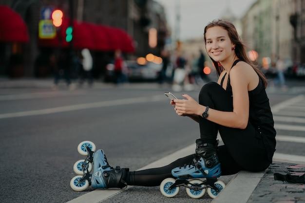 人々の野外活動とレクリエーションの概念。体調の良いアクティブなスリムな女性の横向きのショットは、ローラーブレードに乗ってスマートフォンを使用し、テキストメッセージをオンラインで送信します。