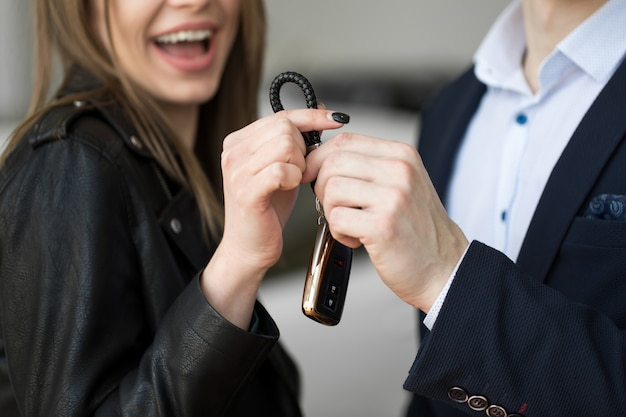 People and ownership concept - close up of car salesman giving key to new owner or customer over auto show