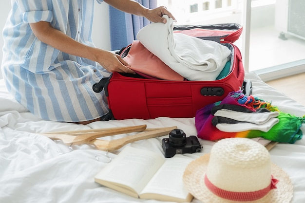 People packed suitcase with travel accessories on bed