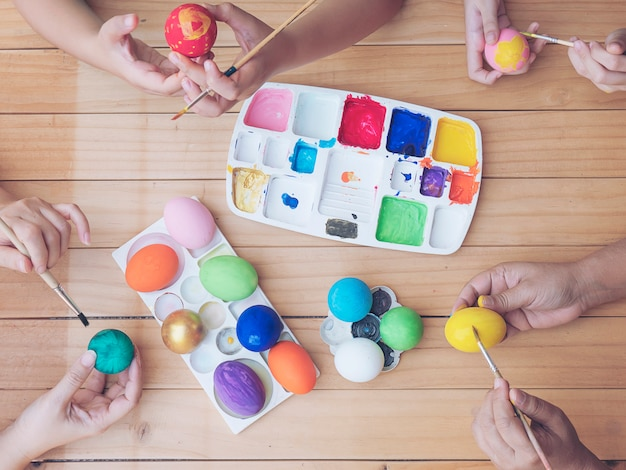 People painting colorful easter eggs - easter holiday celebration concept