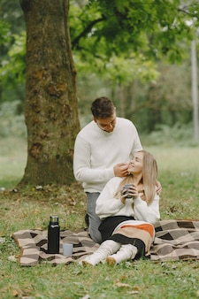 People in a park. woman in a brown coat. man in a white sweater. couple in a picnic.