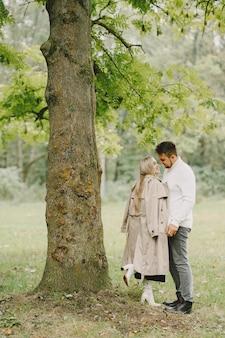 Persone in un parco. donna in un cappotto marrone. uomo con un maglione bianco.