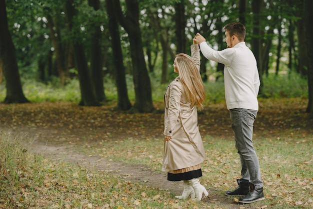 People in a park. woman in a brown coat. man in a white sweater.