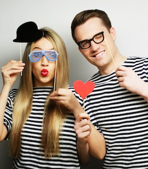 People, party, love and leisure concept - lovely couple holding party glasses and hat on sticks, over gray surface