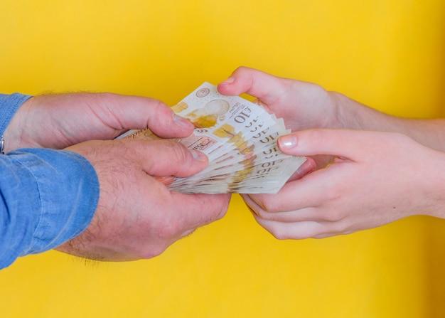 Люди передают деньги друг другу на желтом фоне